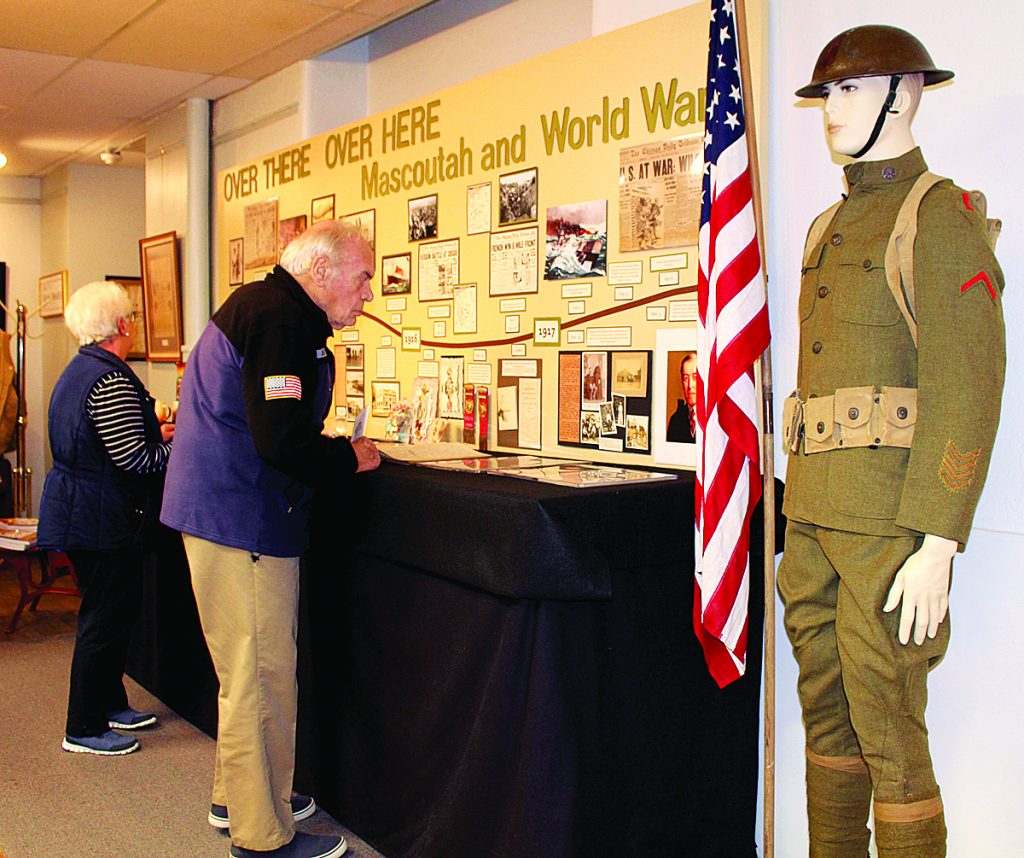 "Visitors to the Mascoutah Museum examine the articles and memorabilia at the opening of their exhibit ""Over There, Over Here...Mascoutah and World War I.""  HERALD"