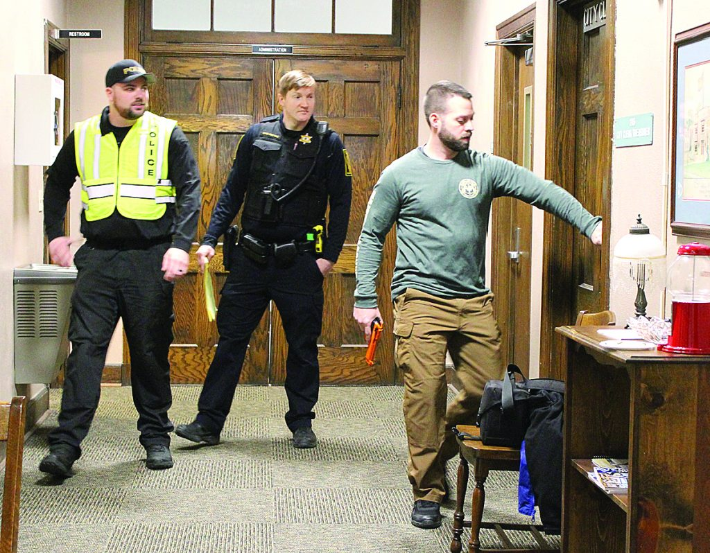 "SWIC Sgt. Jim Watkins and Mascoutah Police Officer Cameron Rettig watch as ""active shooter"" SWIC Sgt. Brandon Borkowski prepares to enter the Mascoutah City Clerk's office.  Watkins and Rettig offered suggestions on how to barracade the different offices to stay safe.  HERALD"