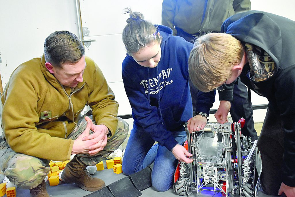 Robo Raider team members Ava Merrifield and Matthew Clayton work with Major Michael Biederman, Cyber Mission Assurance Team Leader at Scott Air Force Base, for a professional design review of their robot and team structure.