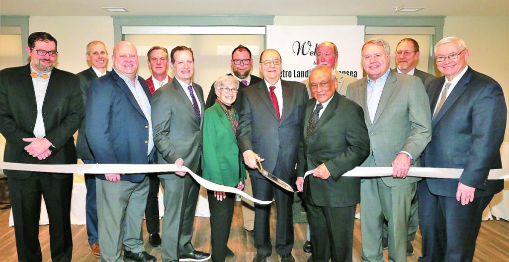Pictured: Former Fairview Heights Alderman James Nations, chairman of the board of directors of the Southwestern Illinois Development Authority, shown here wielding the scissors, Swansea Mayor Mike Leopold, and Illinois State Representative Jay Hoffman were among those present for the ribbon cutting marking the opening of the Metro Landing transit-oriented development project near the MetroLink station in Swansea.