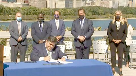 Gov. JB Pritzker signs Senate Bill 2408, a sweeping energy regulation overhaul, into law at the Shedd Aquarium in Chicago Wednesday. (Credit: Blueroomstream.com)